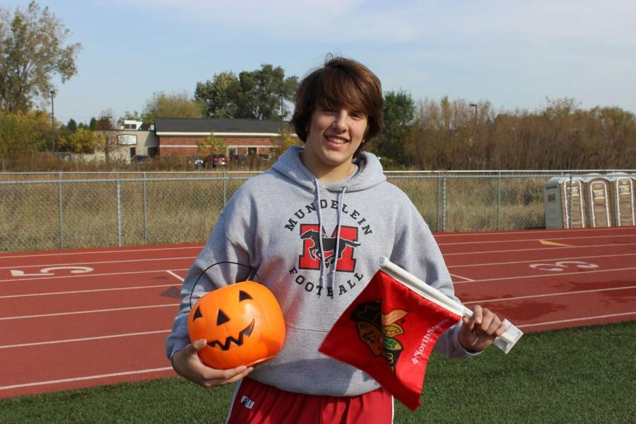 Junior Alex Loding stands with items that represent  his reasons for why he loves fall.