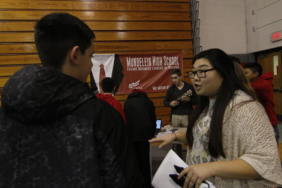 Christine So, sophomore, introuduces an incoming freshman student to Future Business Leaders of America. FBLA was one of the many clubs in attendance at Curriculum Night.