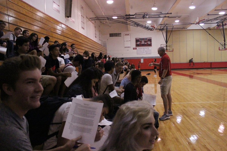 Students go over a class syllabus on the first day of Kevin Evans' Applications of Wellness course.