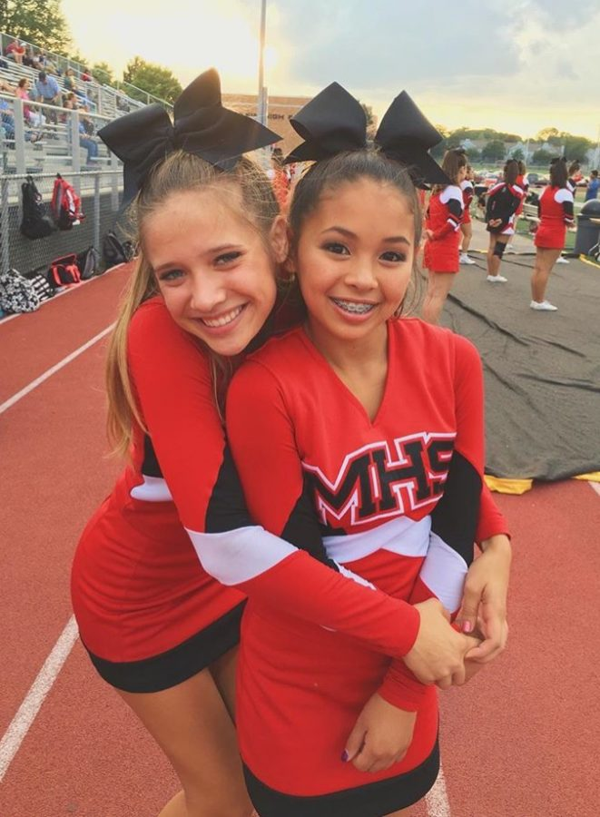 Jessica Nayden, freshman (right), poses with Jessie Kafka, junior (left), at a home football game.