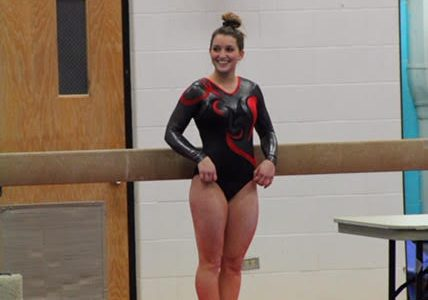 Senior Taylor Shanahan poses in front of the beam before beginning her routine. Shanahan is the captain of the girls gymnastics team.