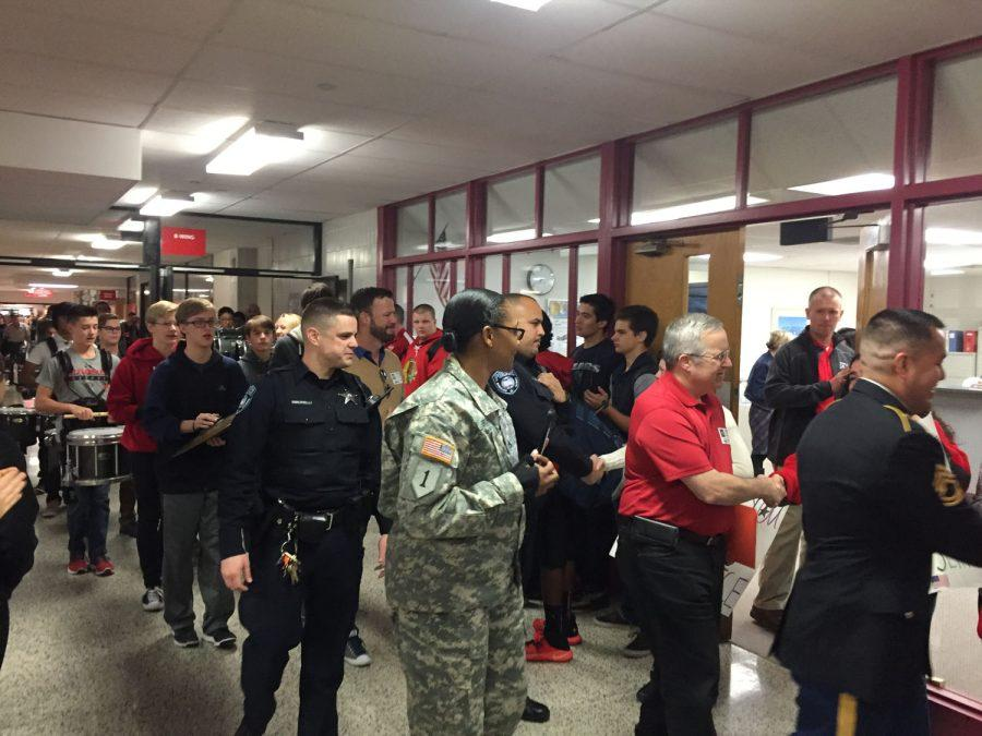 Staff+and+students+greet+Veterans+as+they+enter+the+building+on+Veterans+day.+The+MHS+Marching+Band+led+a+parade+of+Veterans+around+the+school+in+honor+of+their+service+and+sacrifice.
