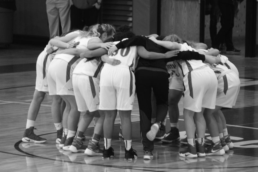 Varsity girls basketball team joins together in a pregame huddle. The team went on to defeat Highland Park on Nov. 14 with a score of 37-35.