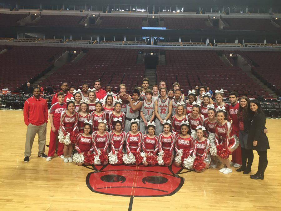 The MHS Boy's varsity baseketball team and cheerleading team take a picture on the United Center court.