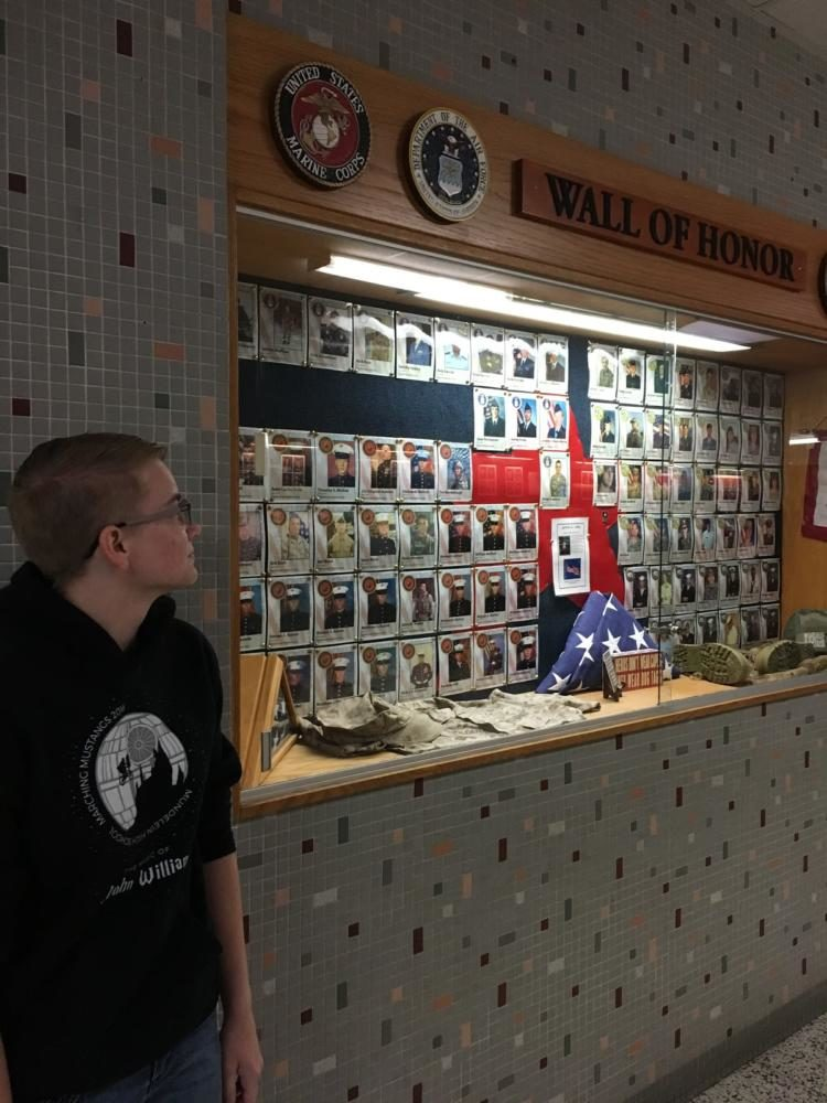 """Shannon Heiberger, U.S. Marines:  Heiberger observes the Wall of Honor at the MHS where past students and staff who served in the United States military are recognized. She decided to join the Marines because she wants a future in law enforcement. She said, """"I wanted to be part of something more important than any individual."""""""