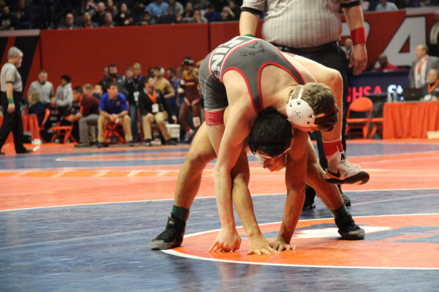 "On Top: Junior Reese Durlacher at 126 pounds loses in his quarterfinal match at the IHSA Individual State tournament in Champaign against senior Jaime Suarez of Wheaton North High School in a decision of 6-4. In his first constellation match, Durlacher wrestled junior Nathan Callaway of Marmion Academy High School, losing in triple overtime by a decision of 6-5. ""At state, you're going up against the top guys in the state, and so all your matches are going to be tough, but you have to just tell yourself that it's do or die right now, and you just have to leave it all on the mat."""