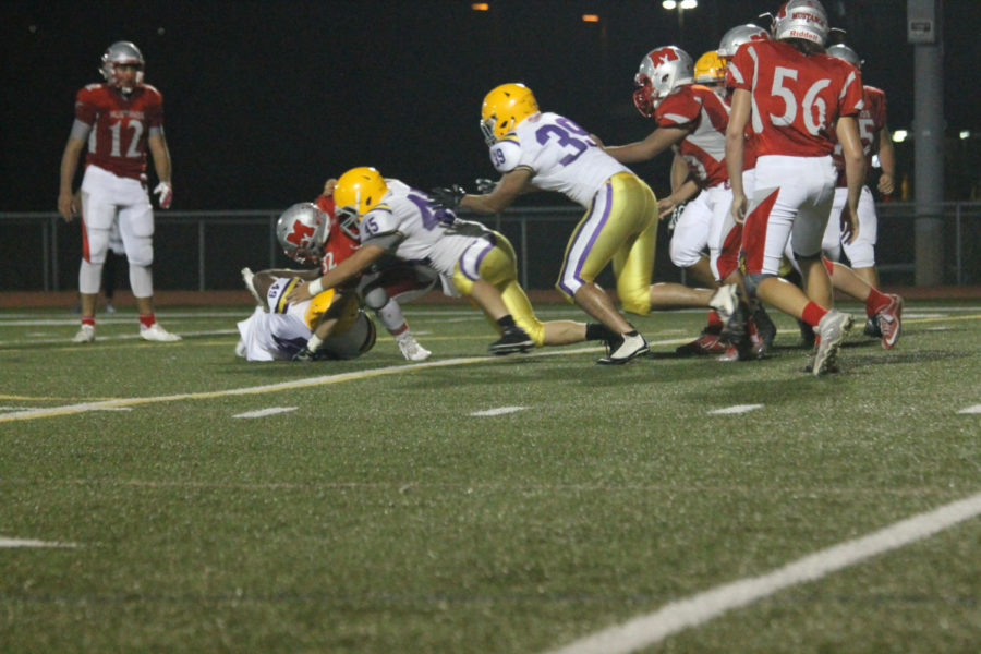 Mundelein running back Kyle Schaller gets tackled by Waukegan defenders during the Homecoming game on Sept. 22.