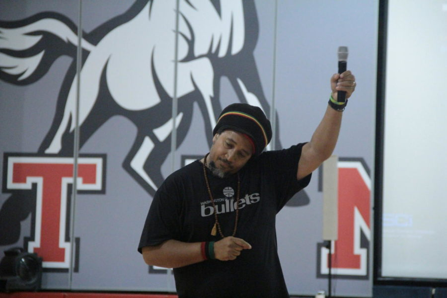 photo by yearbook staff Guest Speaker Calvin Terrell holds up his mic to encourage student engagement with his message during the all-school assembly on Sept. 6.