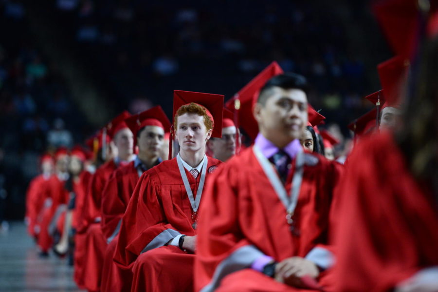 "Graduate Kyle Enright of the Class of 2018 sits among other students during the graduation ceremony at the Sears Centre Arena in Hoffman Estates. Last year's annual event was held on May 13. For the class of 2019, graduation will be held May 12 this year. ""Graduation is important because it's a stepping stone for bigger and better things-- like college, trade school or the army,"" Senior Bryan Silva said."