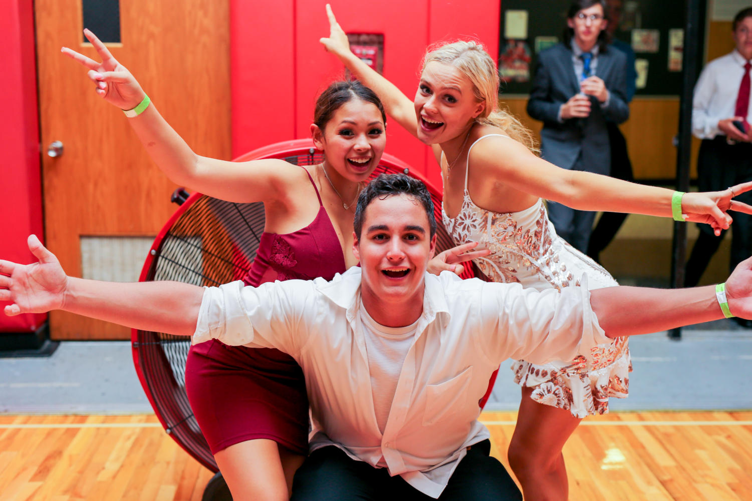 Seniors Jessica Nayden, Sarah Parduhn and Anthony Heelan pose in front of a fan after taking a break from dancing at this year's homecoming dance.