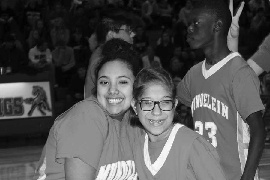 """Nothing but smiles: Right, freshman Princessa Vazquez and junior Neila Stevenson smile together during their warmups for their big game against the Warren Blue Devils. Stevenson later commented that """"shooting buckets"""" was her favorite part of the game."""