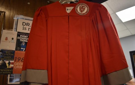 A red graduation gown featuring an older, now outdated, MHS patch and shield.