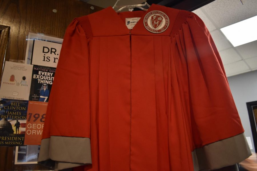 A+red+graduation+gown+featuring+an+older%2C+now+outdated%2C+MHS+patch+and+shield.+