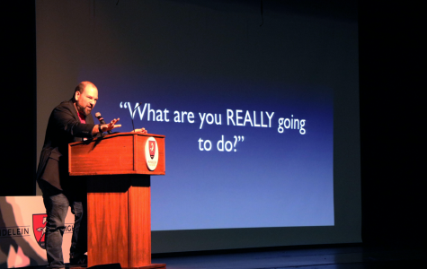 While explaining his background, guest speaker Barry Lyga, promotes his books to his audience on Feb. 25 in the school Auditorium. Lyga engaged his listeners with