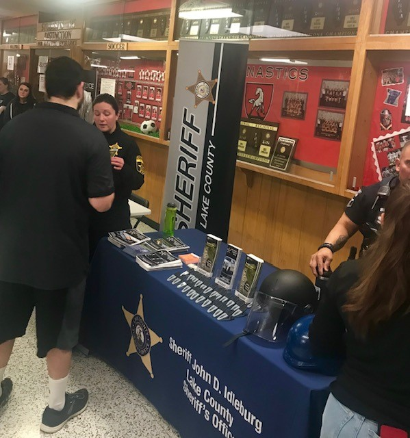 Students Engaged: Lieutenant Sara Balmes and senior Shan Haque discuss information regarding the several summer police employment opportunities offered for teens and adults interested in training as a sheriff at the Lake County Sheriff Office in Waukegan.