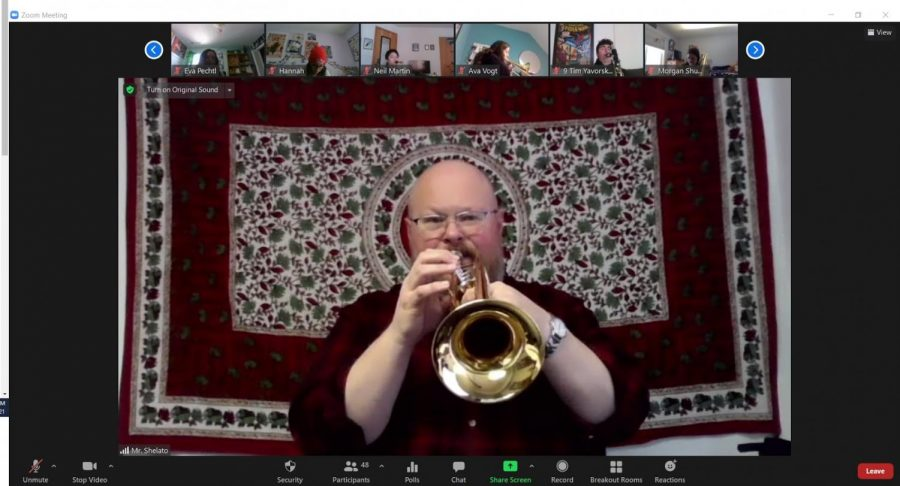 """While performing the group's music, Band Director Jerald Shelato plays his trumpet during 5th period on Zoom, unmuted, for the Honors Wind Ensemble musicians to play along with at home. """"Students, you may or may not believe this, but to whatever degree you find online band to be cold, lacking, without spark, etc., so do I,"""" Shelato said. """"I want us to get back to regular in-person band as soon as we can safely do it."""""""