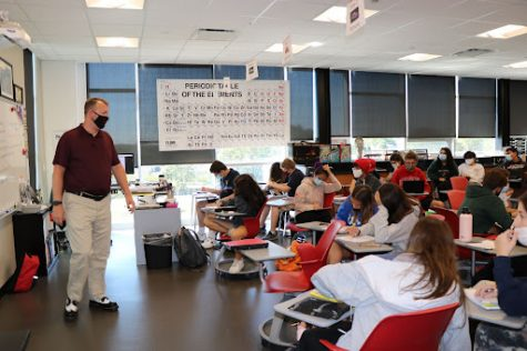 """Science Teacher Chris Michalides teaches his third period Honors Chemistry class, discussing how the metric system functions. He said he has looked forward to a return to in-person learning, to go back to the teaching style he had before remote learning. """"I can monitor more students accurately and conveniently when in person,"""" he said. """"Science is inherently hands-on for students and for me. Time to bring back the cool and dramatic demonstrations that make science interesting for many."""""""